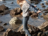 A woman on a rocky coastline on an autumn afternoon in Palos Verdes, CA on November 11, 2011.  Model Released.  Danielle Pascente.